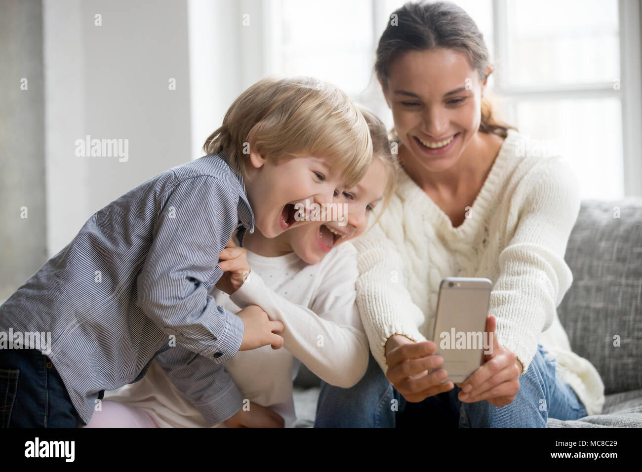 smiling mother taking selfie with cute kids on smartphone, happy