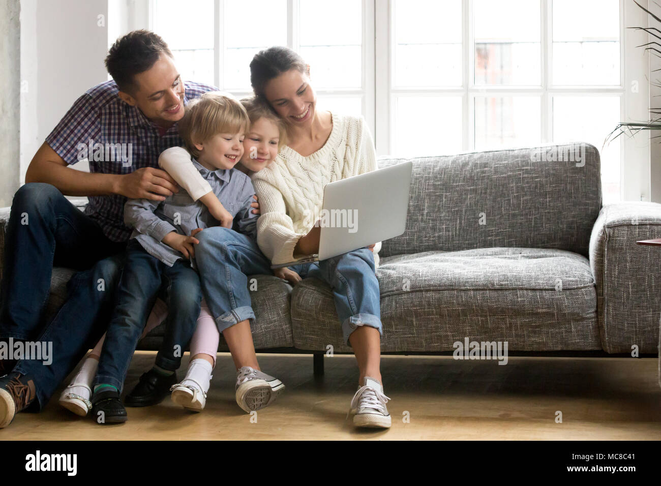 Happy family with little kids enjoying using application on laptop together, smiling parents spending time with children son and daughter having fun w - Stock Image