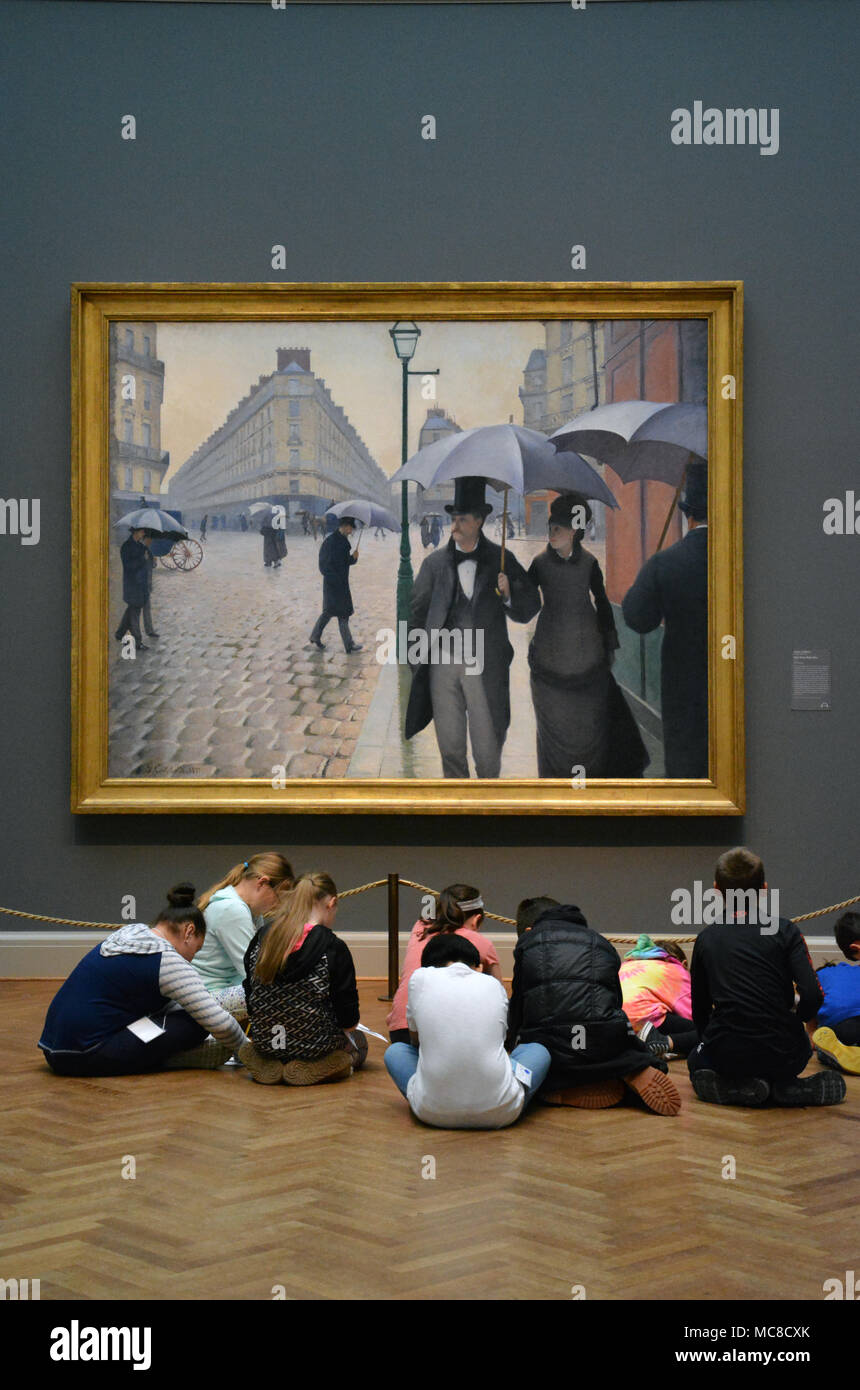 Young children sit on the floor sketching the painting, Paris Street, Rainy Day, in the French Impressionism gallery at the Art Institute of Chicago - Stock Image