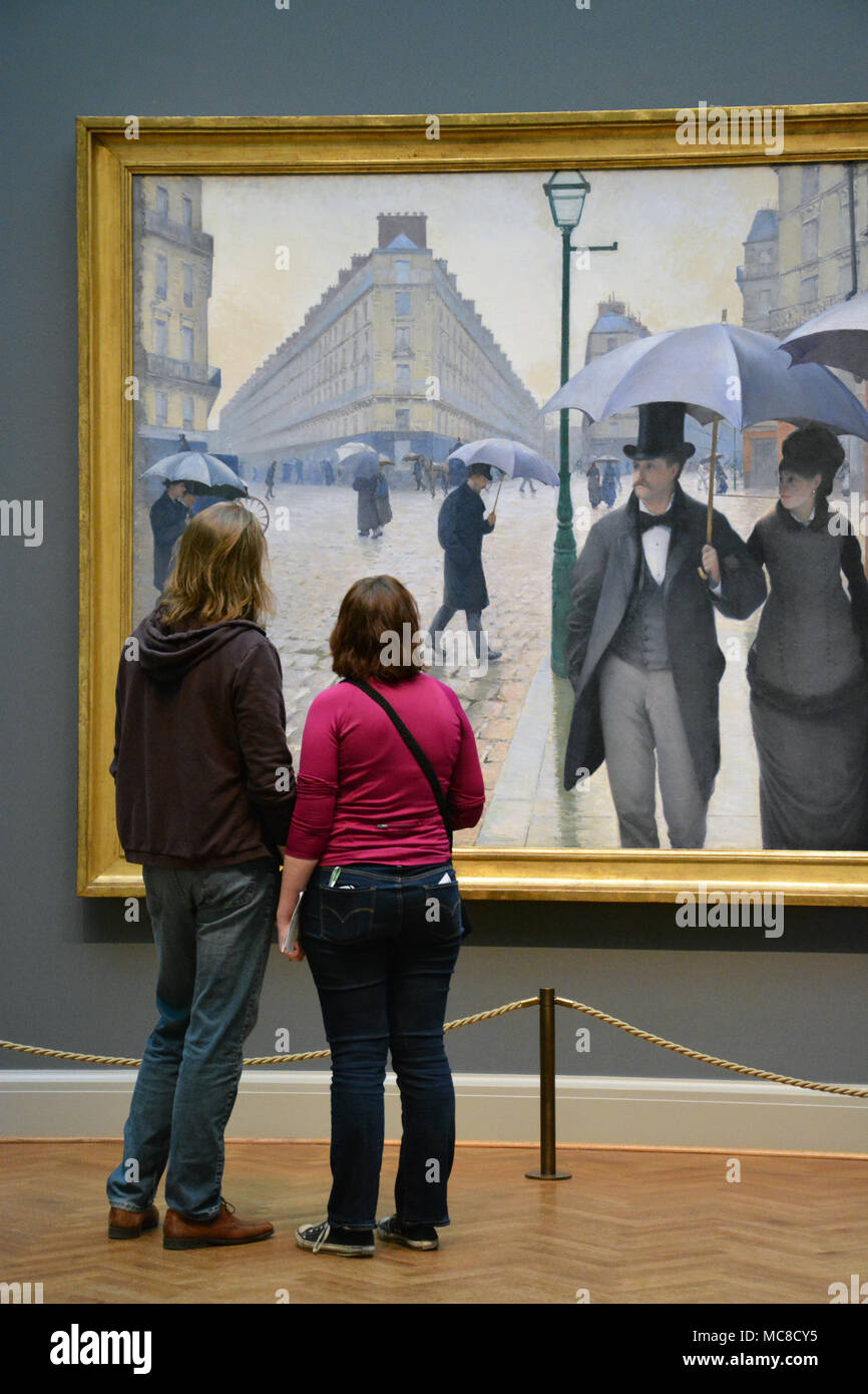 A couple views the painting, Paris Street, Rainy Day, in the French Impressionism gallery at the Art Institute of Chicago - Stock Image