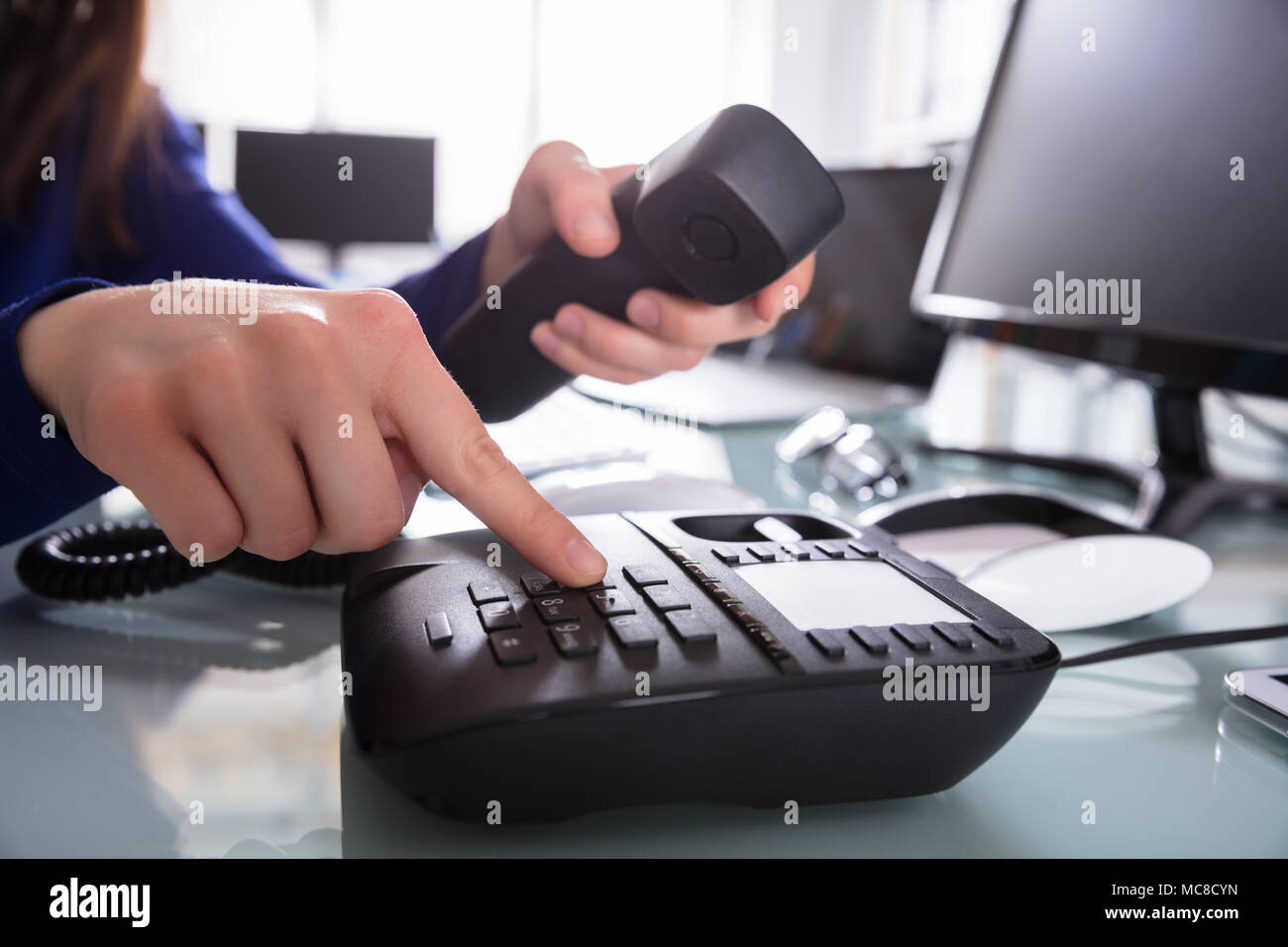 Close-up Of A Businessperson's Hand Dialing Telephone Number To Make Phone Call - Stock Image