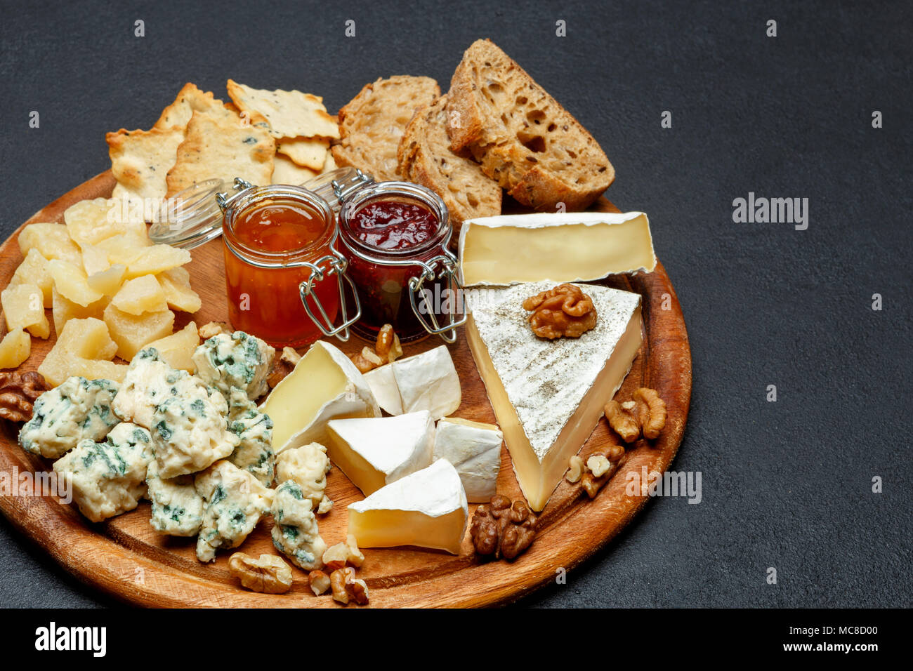 Brie cheese on a wooden Board with bread and sweet jam - Stock Image
