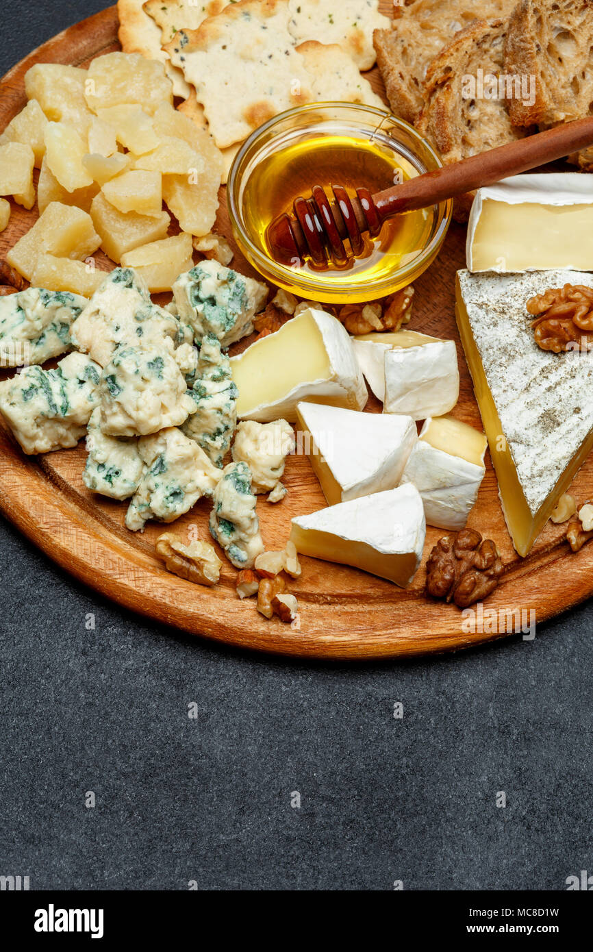 Brie cheese on a wooden Board with bread and sweet honey - Stock Image