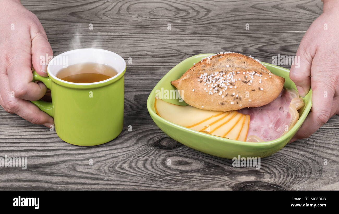 Hands are serving hearty breakfast with hot tea. Green bowl, salty bread roll, sliced ham hock and edam, mug with the smoking drink on wood background. - Stock Image