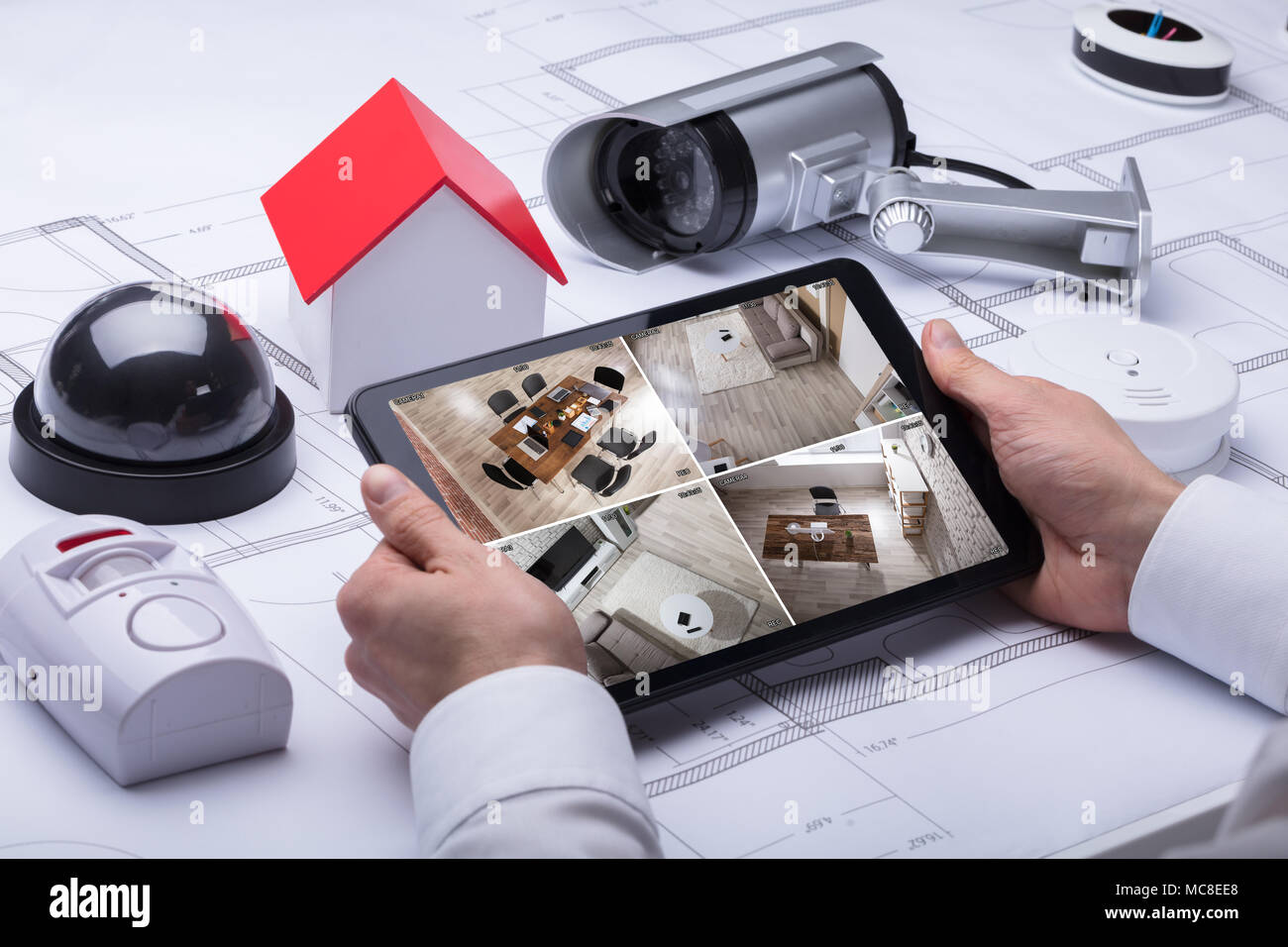 A Person Watching Footage On Digital Tablet With Security Equipments And House Model On Blueprint - Stock Image