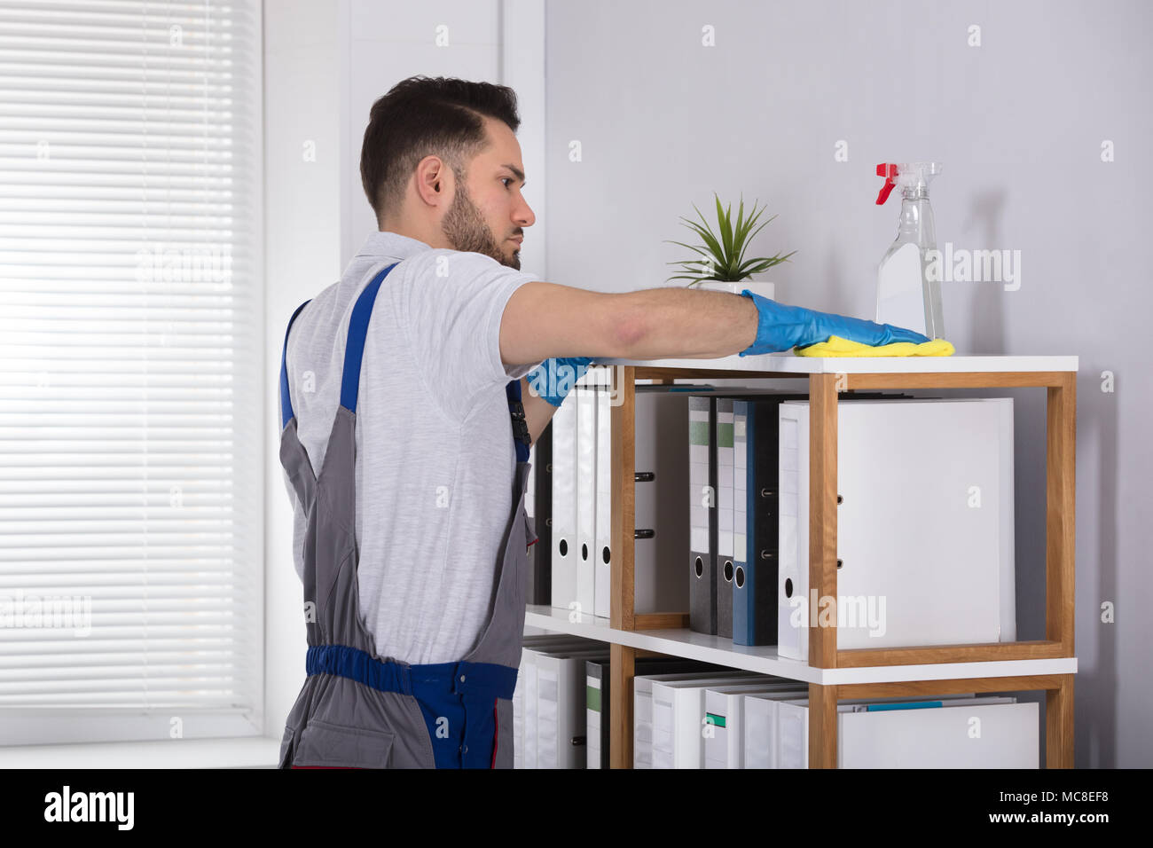 Close-up Of A Young Male Cleaner Cleaning Shelf At Workplace Stock Photo