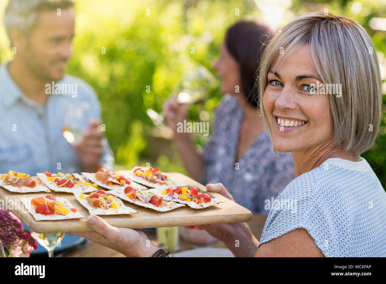 In summer. Group of friends gathered around a table in the garden to share a meal. a beautiful woman serves them snacks on a platter while looking at  - Stock Image