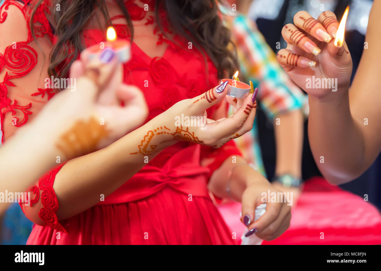 Hands and fingers are drawn to henna . Female hand with henna tattoo . . She holds the candle in his hand Henna party Stock Photo