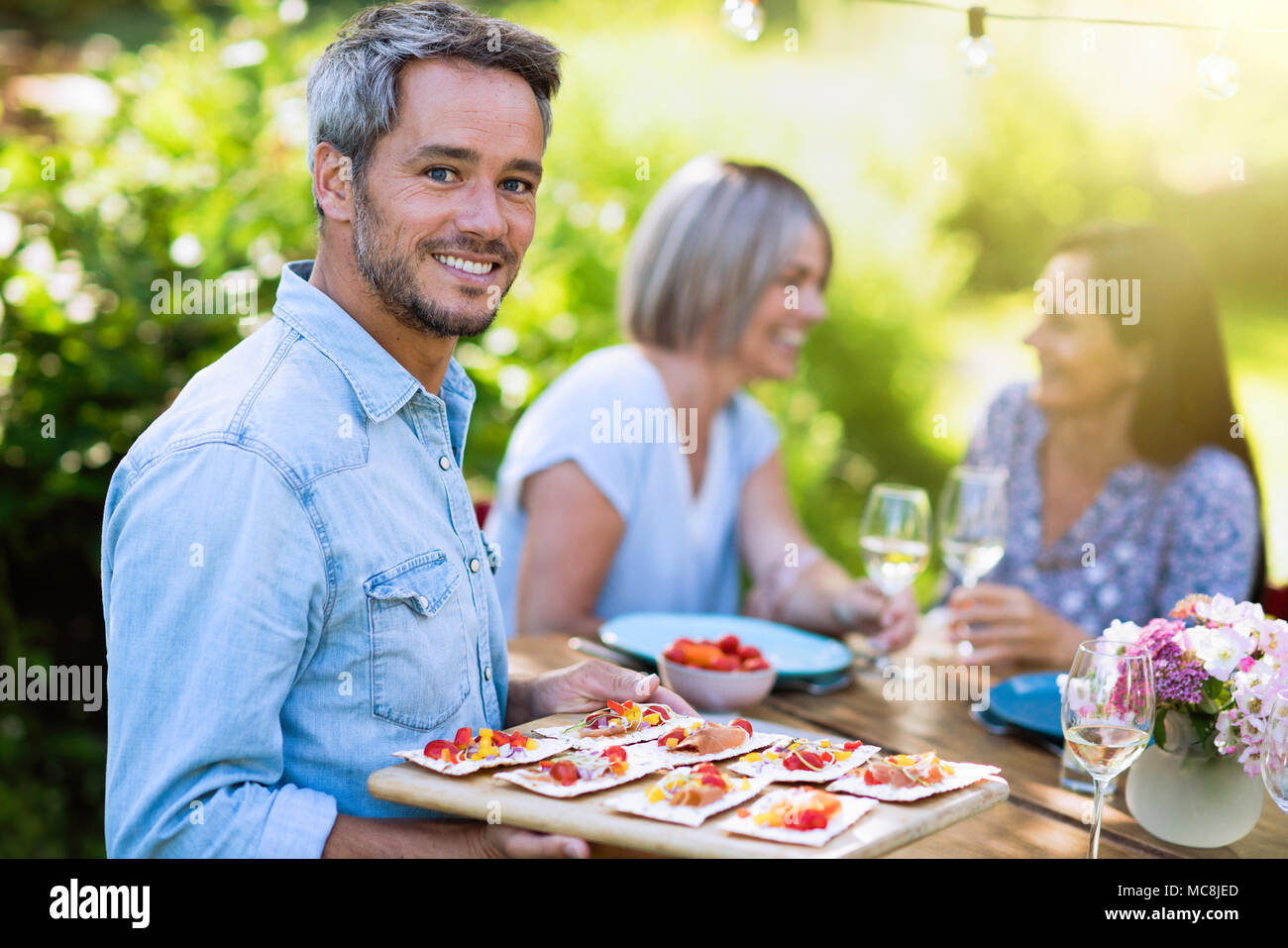 group of friends in their forties gathered around a table in the garden to share a meal. A man offers snacks to guests while looking at the camera - Stock Image