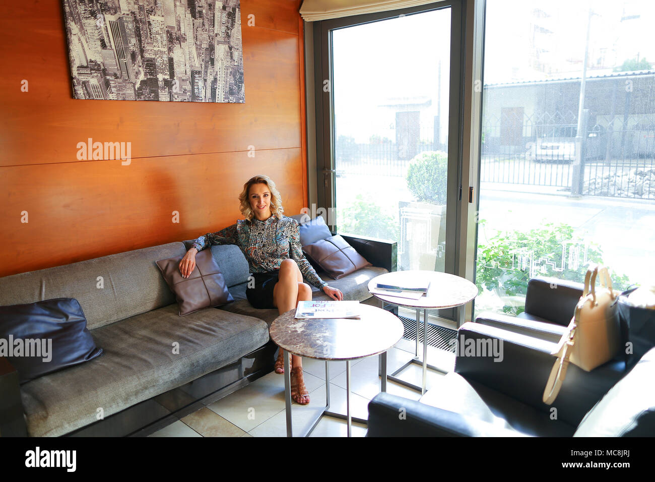 Woman Sitting On Sofa Near Window At Home Stock Photo 179669942 Alamy