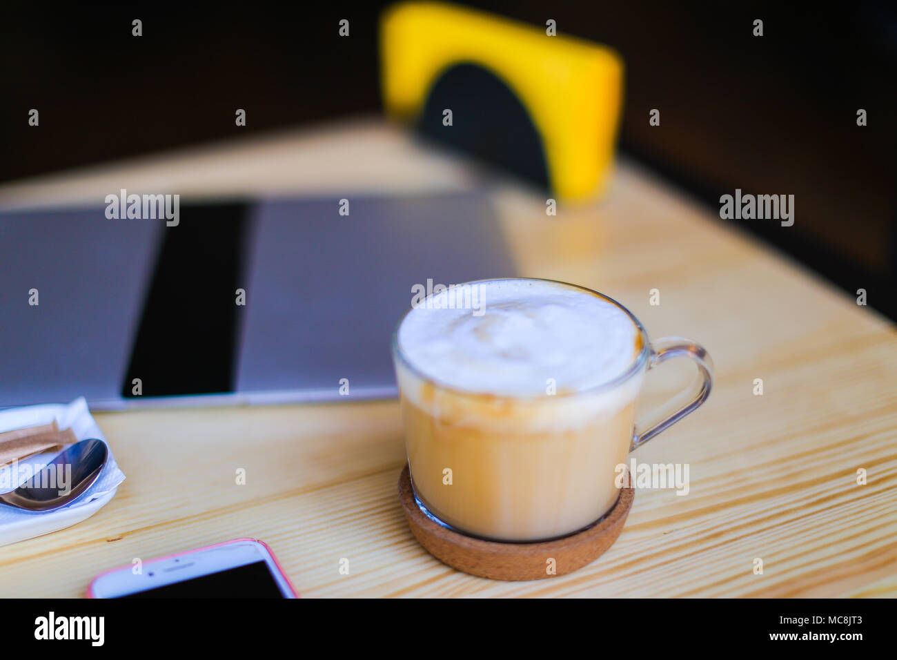 Cafe visitor made photo of table with cappuccino, laptop, smartphone.  - Stock Image