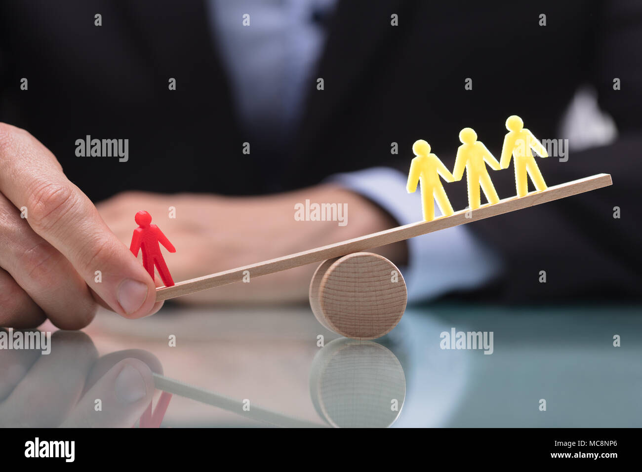 Businessperson's Hand Showing Imbalance Between Red Figure And Three Yellow Figures On Seesaw Stock Photo