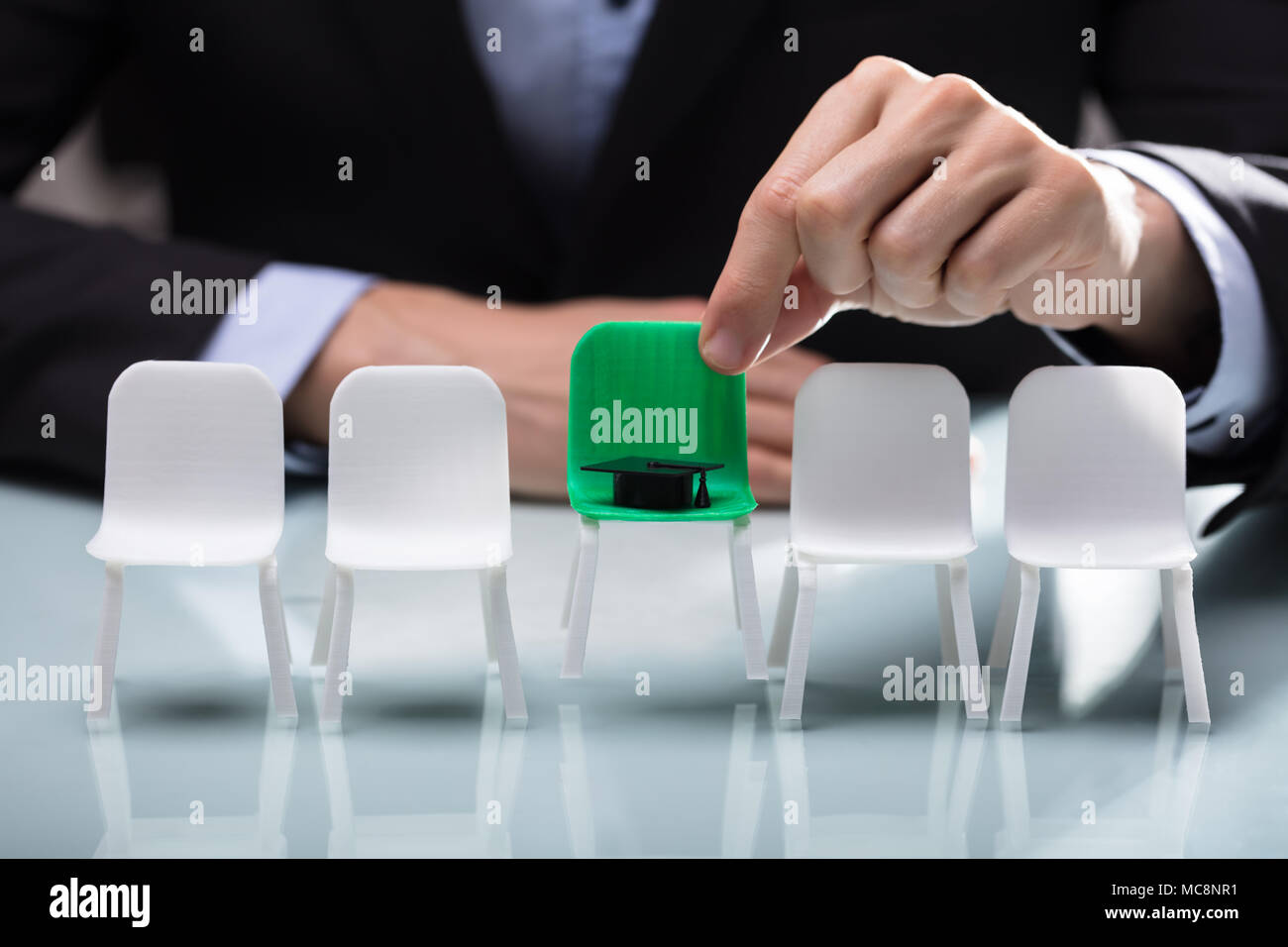 Close-up Of A Businessperson's Hand Choosing Green Chair With Graduation Hat Stock Photo