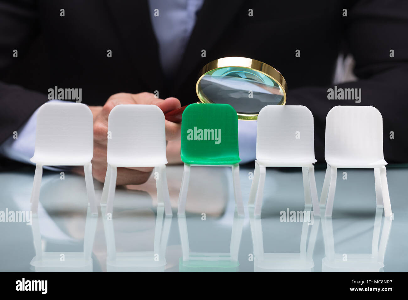 Close-up Of A Businessperson's Hand Looking At Vacant Chairs Through Magnifying Glass Stock Photo