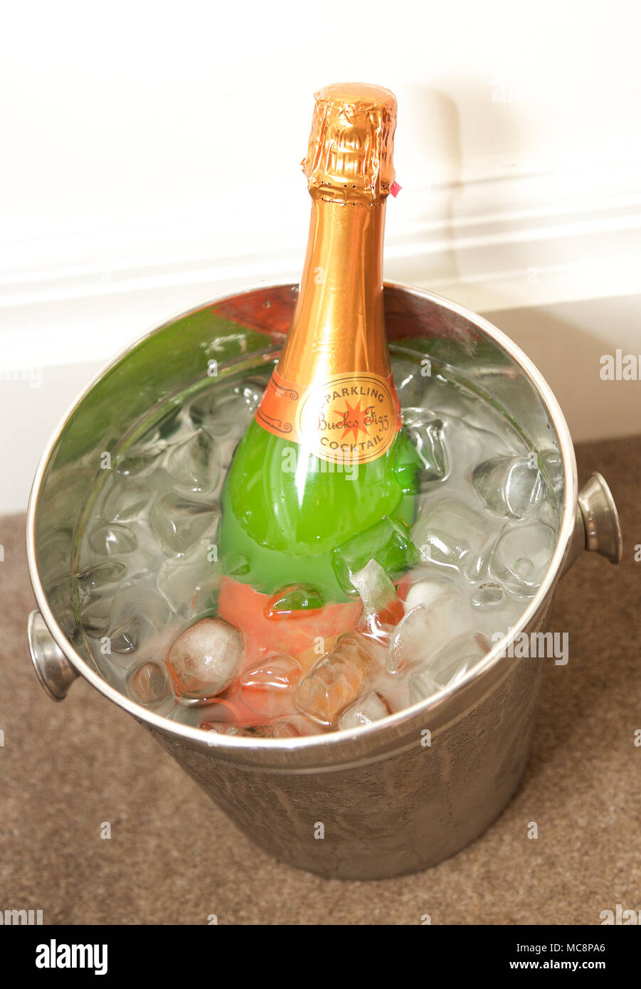 Bottle of Bucks Fizz in an ice bucket - Stock Image