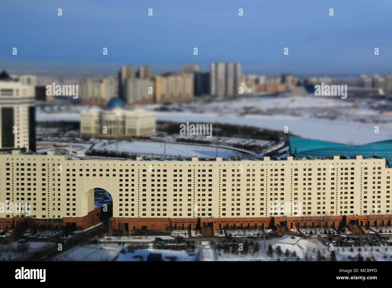 Soviet Style Building in Nur-Sultan, Kazakhstan, at -24 degrees Celsius - Presidential Palace in the background - Stock Image