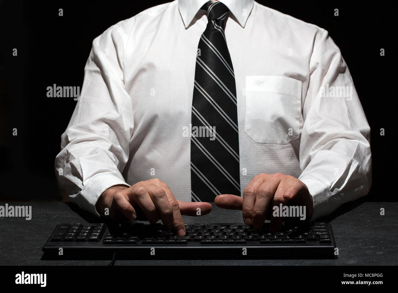man wearing white shirt with black tie has stripes on it while typing - Stock Image