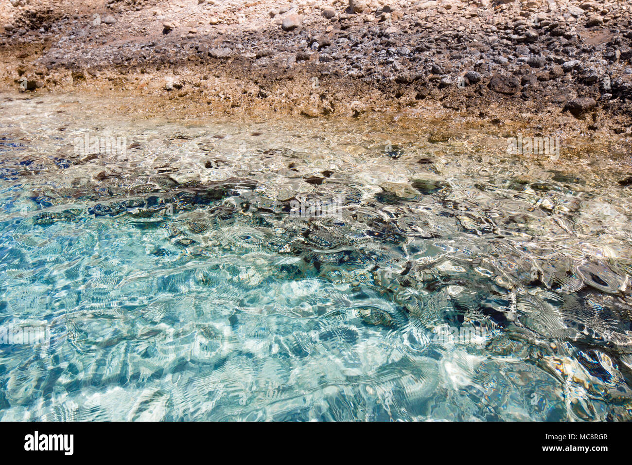 Cristal clear turquoise water and the sea urchins on the bottom, coast of Crete, Greece. wave pattern, wind ripples the sea surface. Sun reflections. - Stock Image