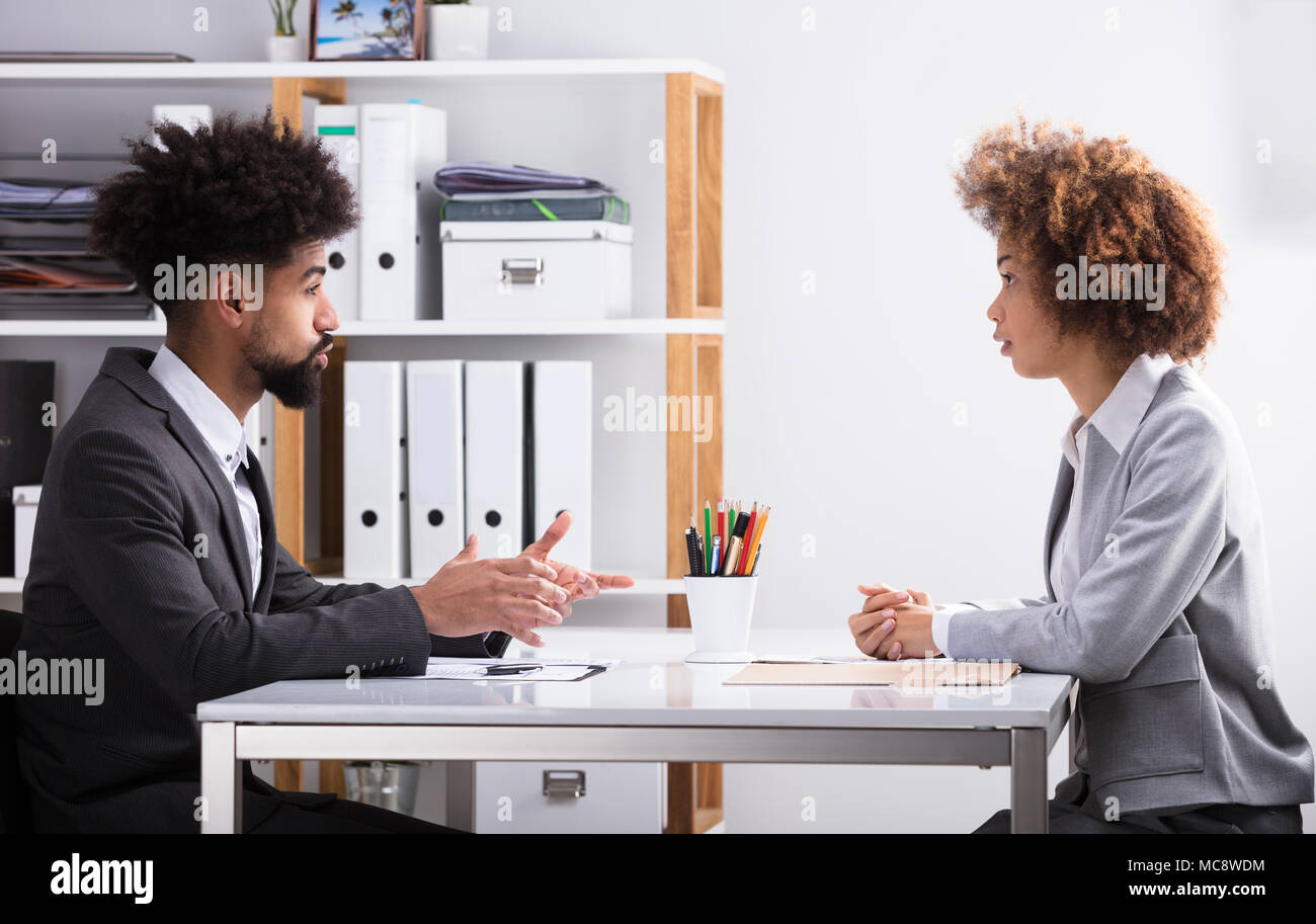 Side View Of Two Young Businesspeople Having Conversation In Office - Stock Image