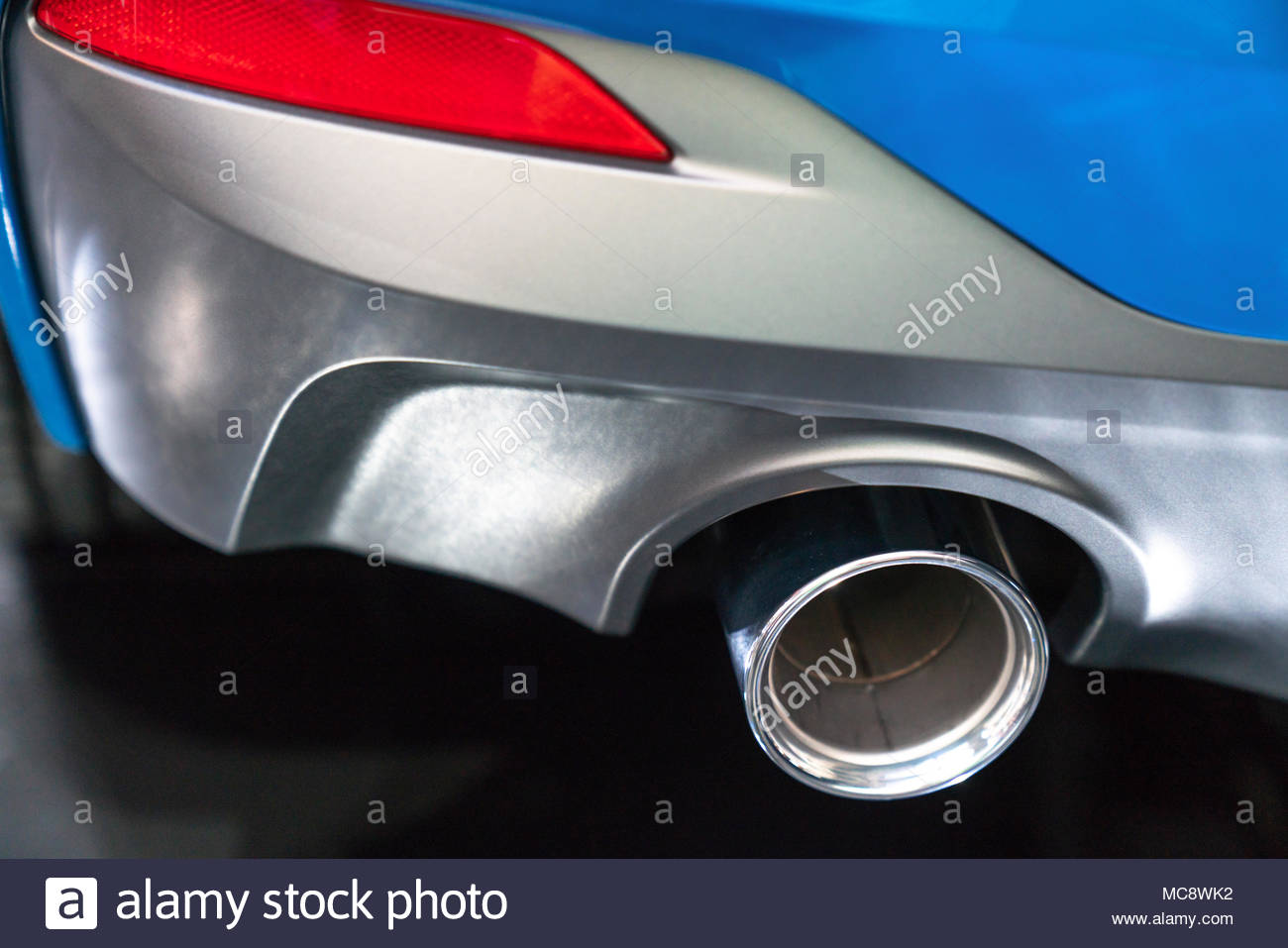 New generation of sportive mufflers. Oval Car Exhaust Tailpipe chromed made of stainless steel on powerful sport car bumper. Close up & New generation of sportive mufflers. Oval Car Exhaust Tailpipe ...