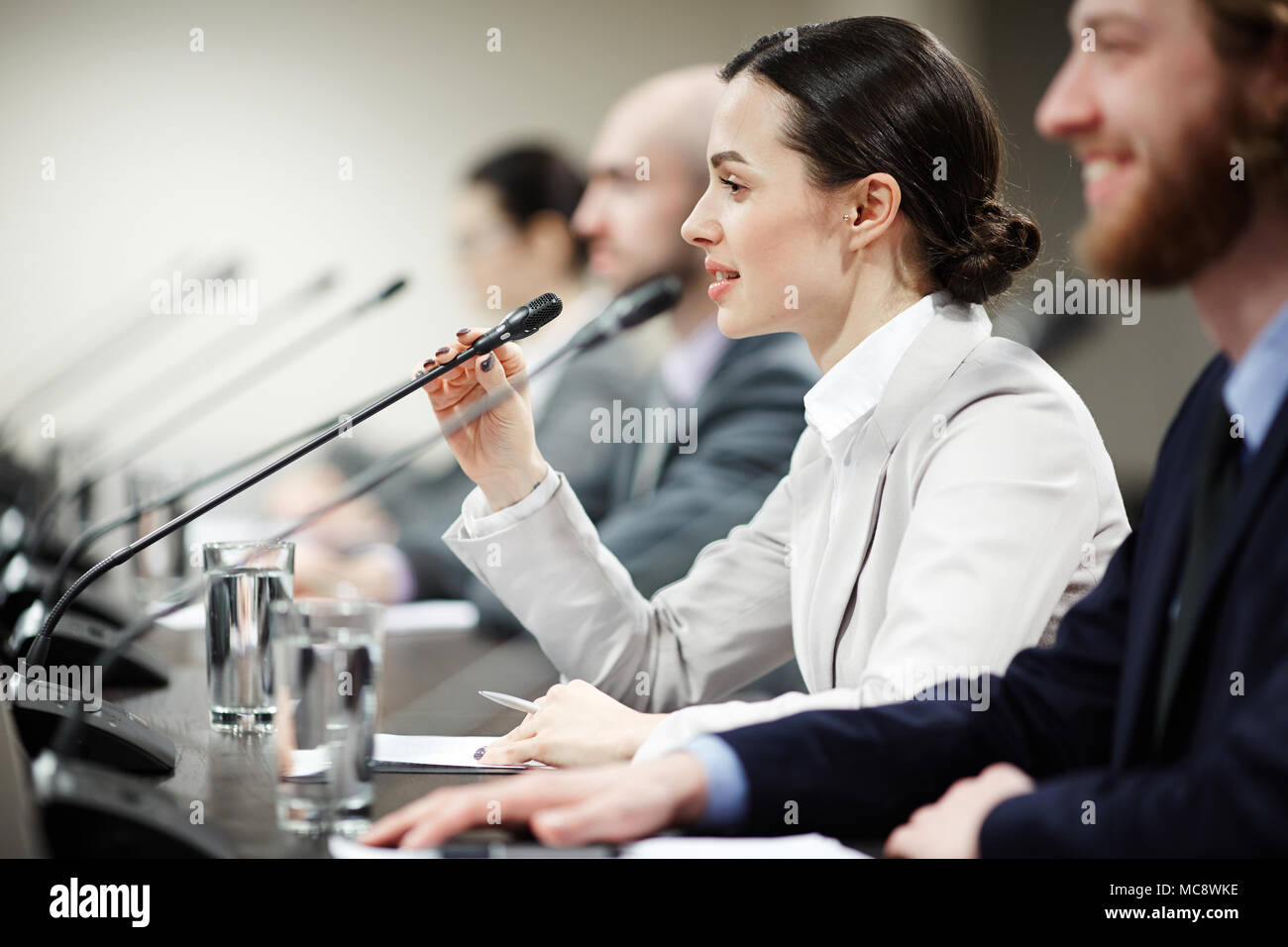 One of young politicians speaking in microphone among other participants of conference - Stock Image