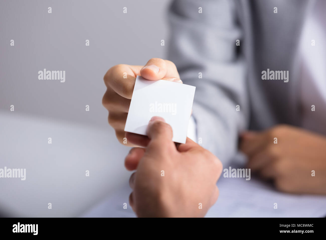 Close-up Of Businessperson's Hand Giving Blank White Card To Partner Stock Photo
