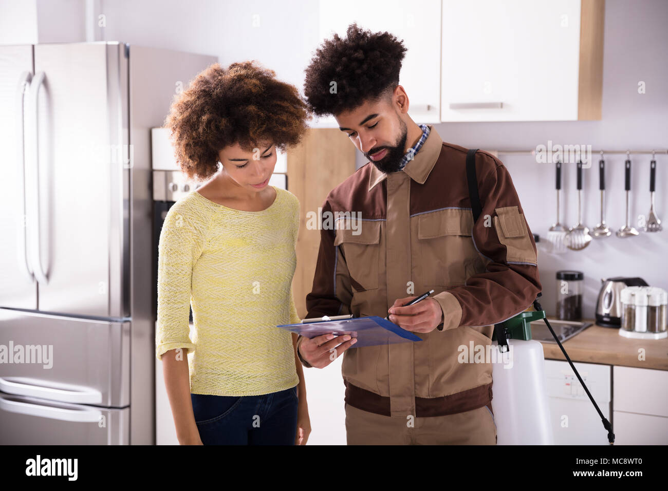 Young Male Pest Control Worker Showing Invoice To Woman In Domestic Kitchen - Stock Image