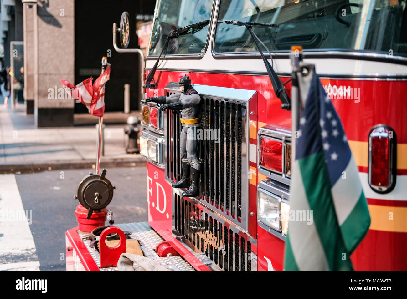 Detailed, shallow focus of the front of an FDNY truck showing a super-hero toy attached to the grill. Coachwork detail visible, seen at a junction. - Stock Image