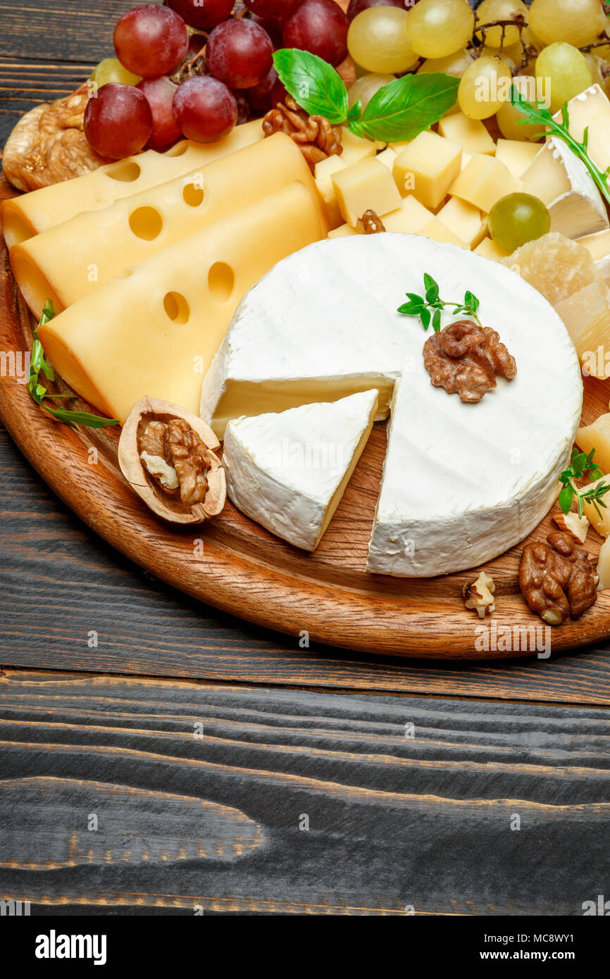 various types of cheese on wooden cutting board Stock Photo