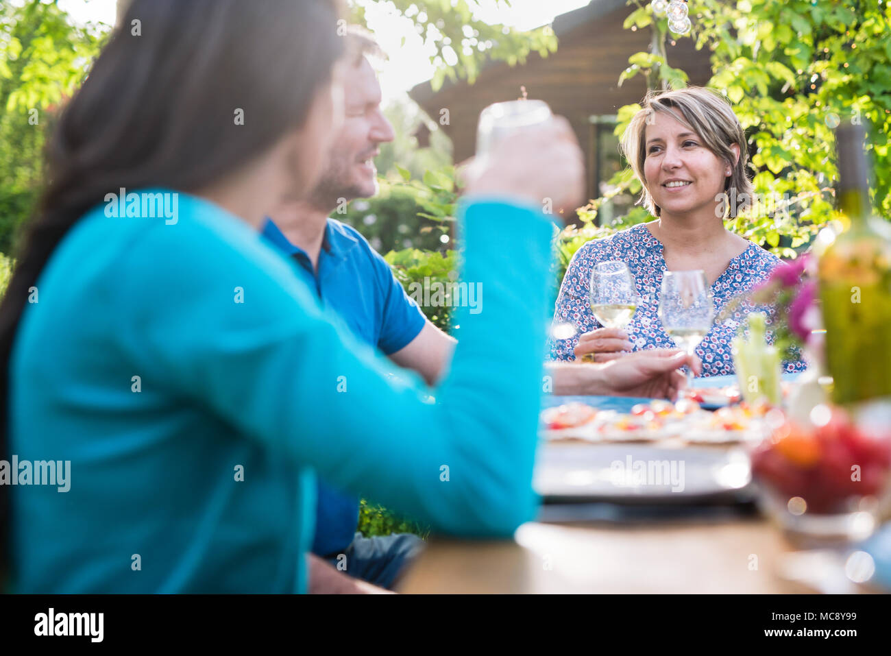 Friends gathered around a table in the garden one summer evening to share a meal and have fun together. - Stock Image