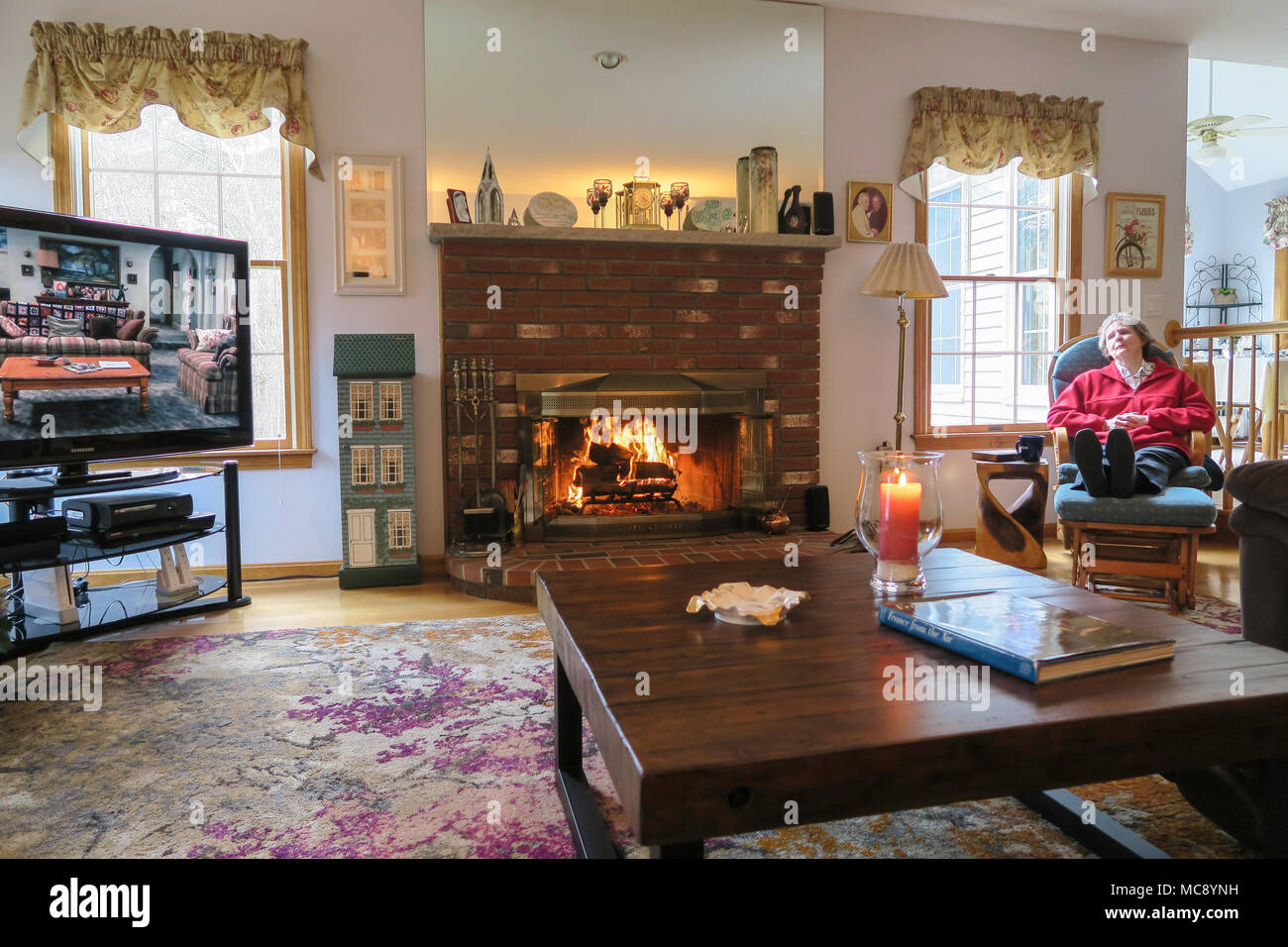 Inviting Family Room with Fire in Fireplace, USA - Stock Image