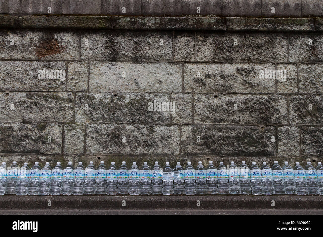 Water bottles lined up against a wall in a effort to keep cats away from the area. Sengoku, Tokyo, Japan. Friday March 23rd 2018 - Stock Image