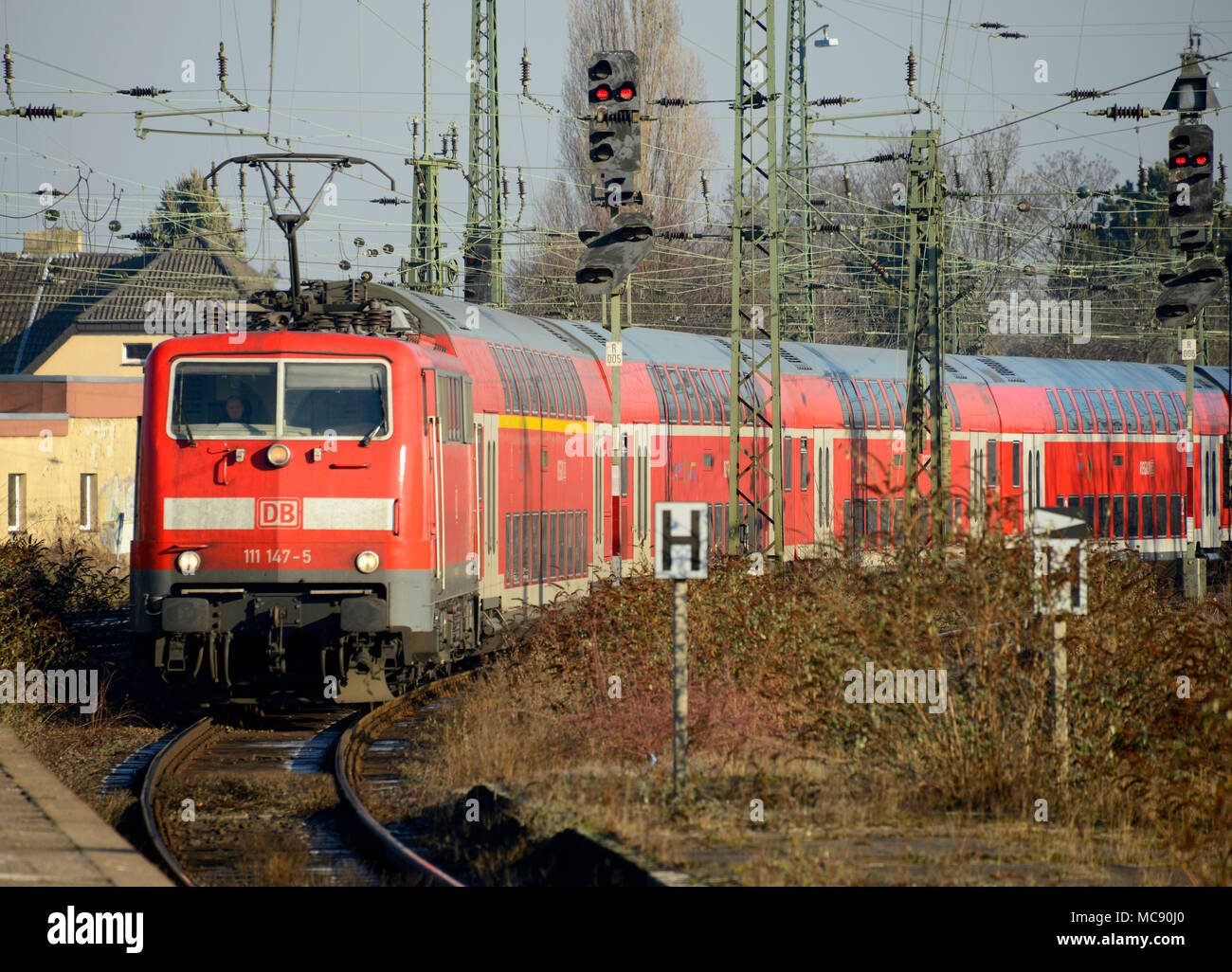 A DB service hauled by a class 111 locomotive approaches Monchengladbach station in Germany - Stock Image