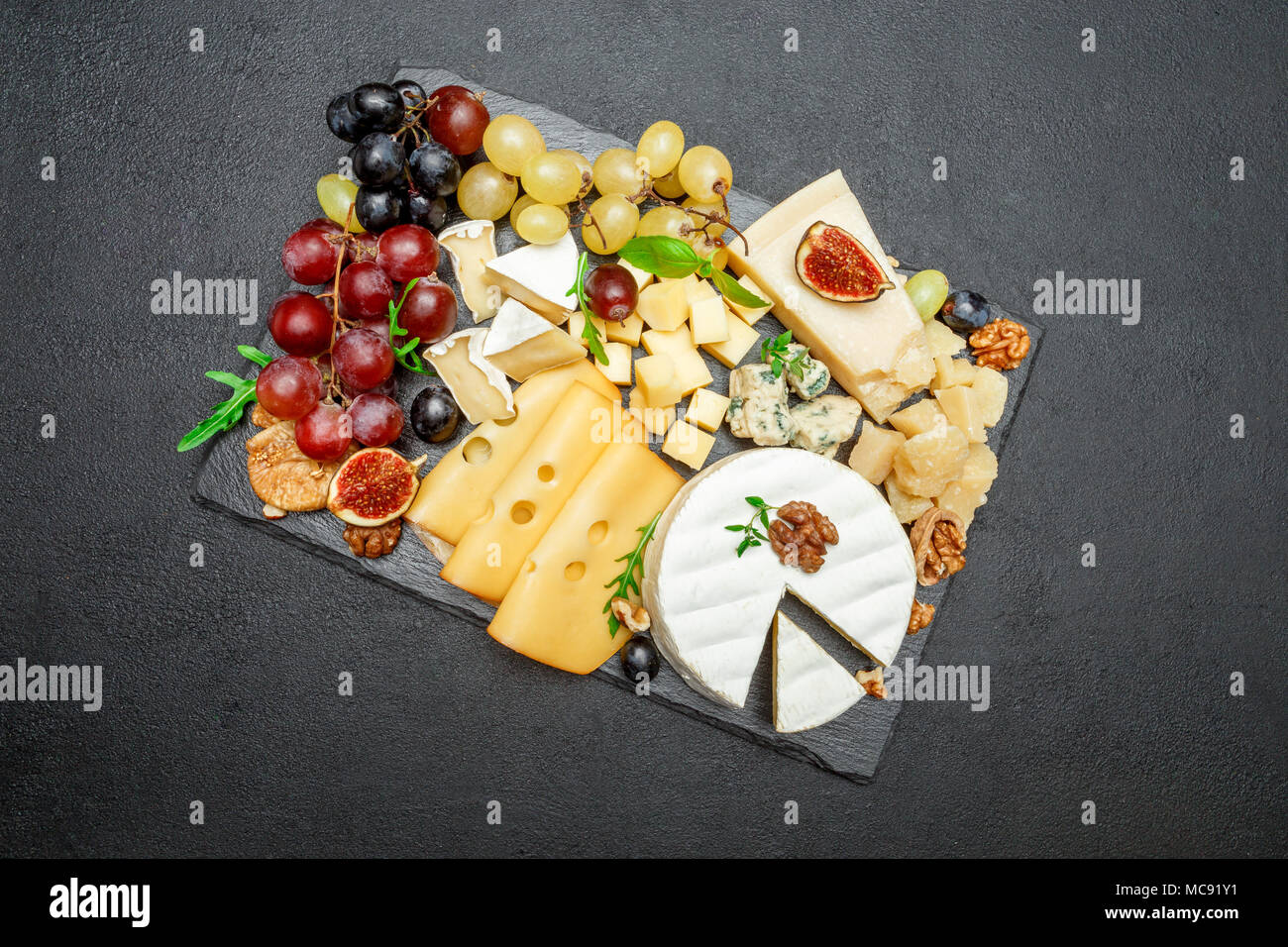 various types of cheese on stone serving board Stock Photo