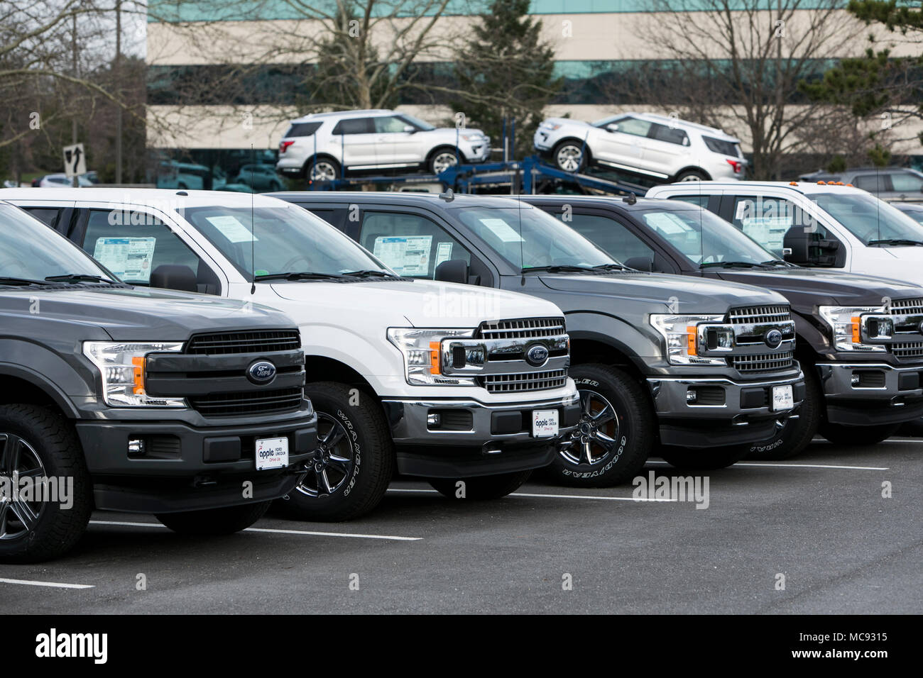 A row of new Ford F-series pick-up trucks and Explorer SUV's at a car dealership in Columbia, Maryland on April 13, 2018. - Stock Image