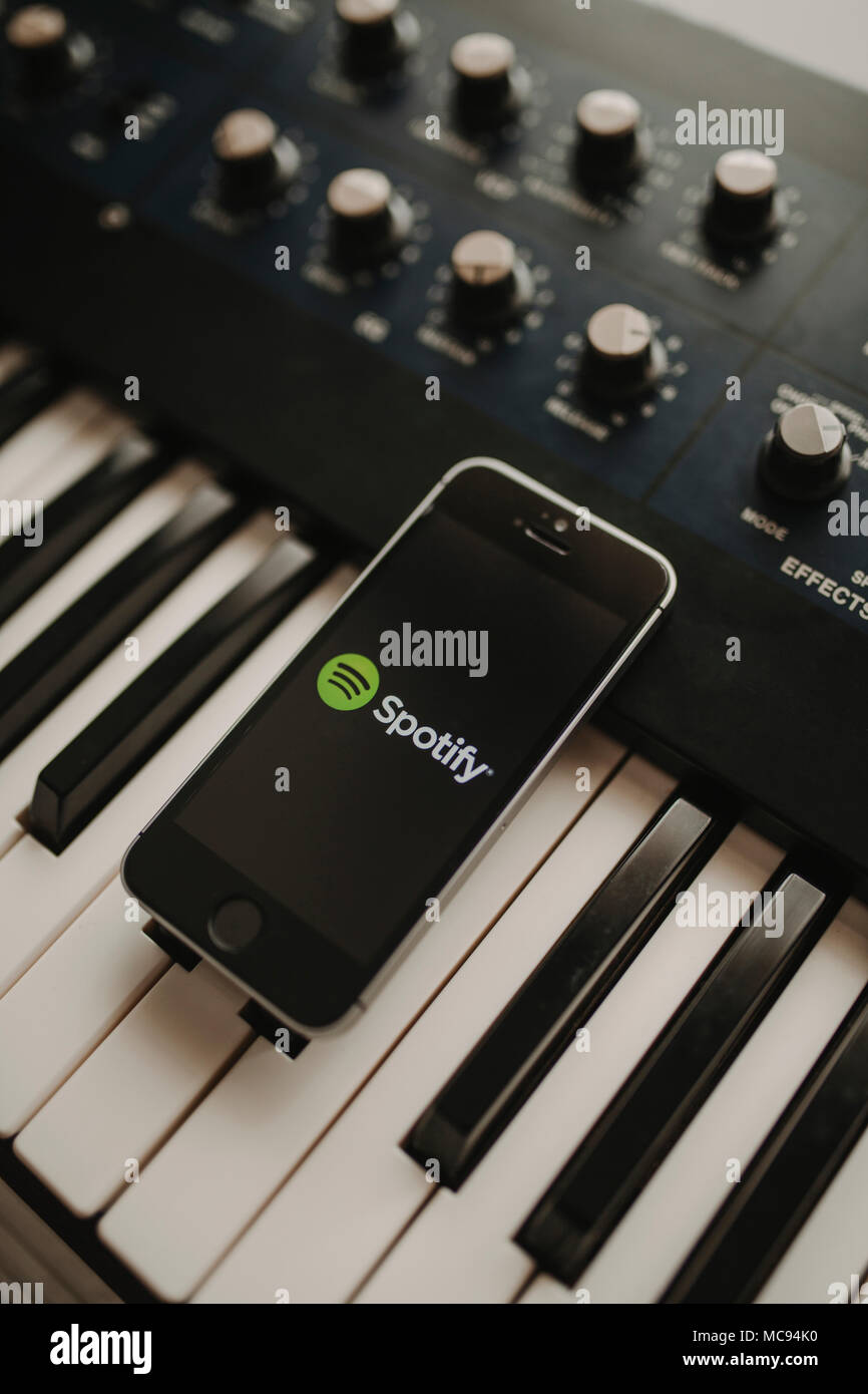 Close up of mobile phone with Spotify logo in the screen and white earphones, placed over a organ keyboard, in Malaga, Spain, on March 3th, 2018 - Stock Image