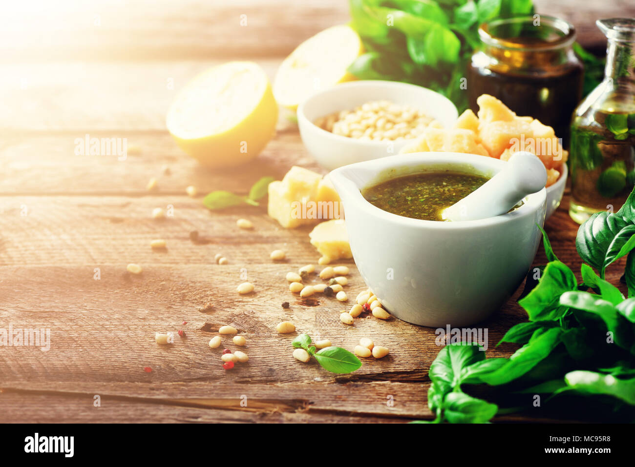 Ingredients for homemade pesto - basil, lemon, parmesan, pine nuts, garlic, olive oil and salt on rustic wooden background. Top view, flat lay, copysp Stock Photo
