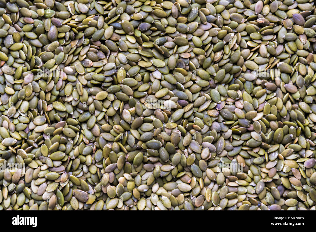 Full frame close-up raw pumpkin seeds in flat lay format - Stock Image
