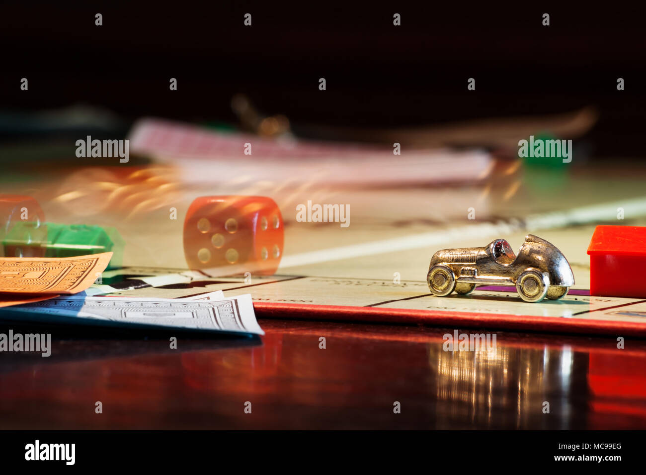Salzburg, Austria - April 6 2010: Monopoly boardgame with rolling dice behind car - Stock Image