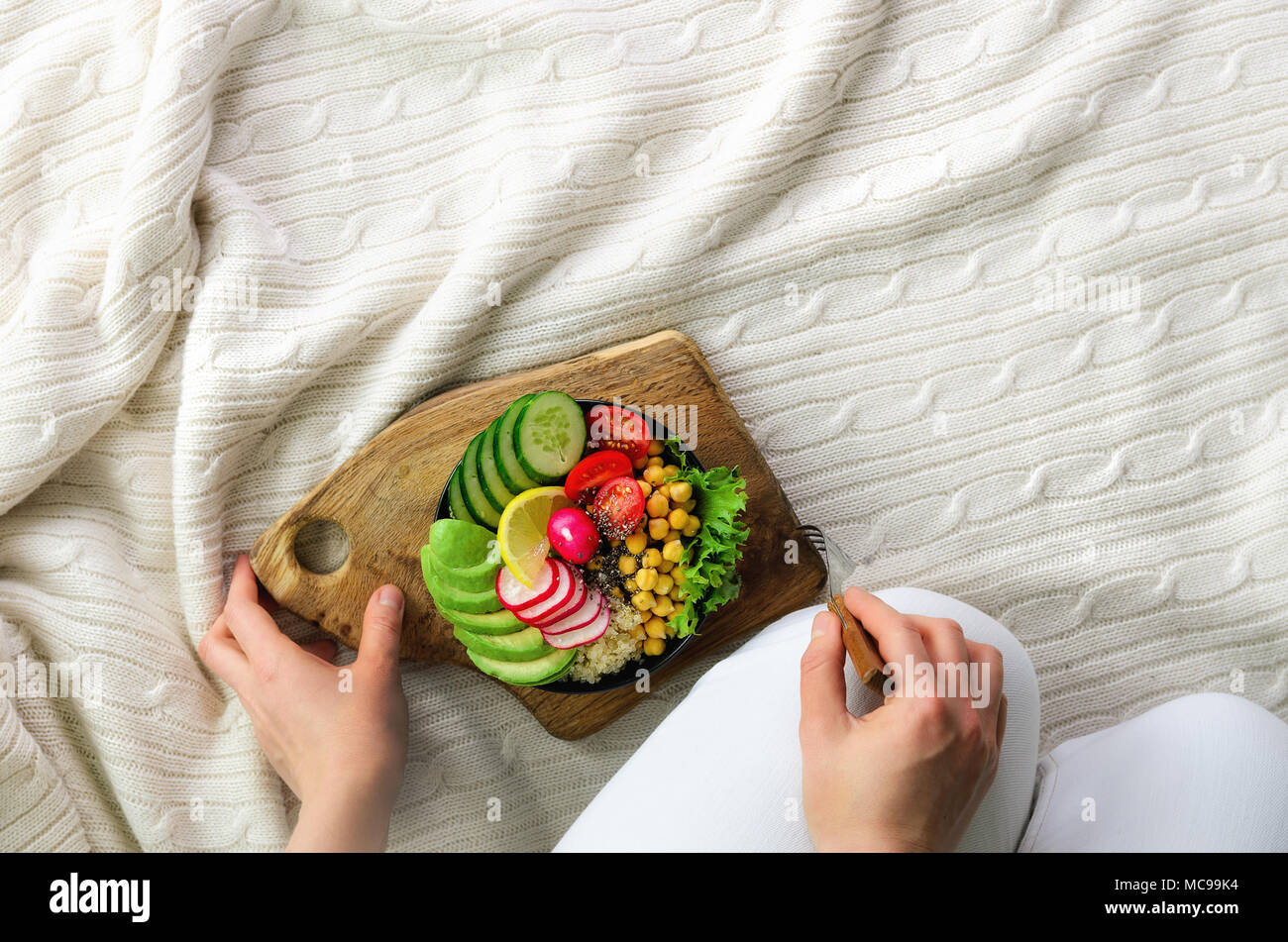 Girl in white jeans holds in hands fork, vegan breakfast meal in bowl with avocado, quinoa, cucumber, radish, salad, lemon, cherry tomatoes, chickpea, - Stock Image