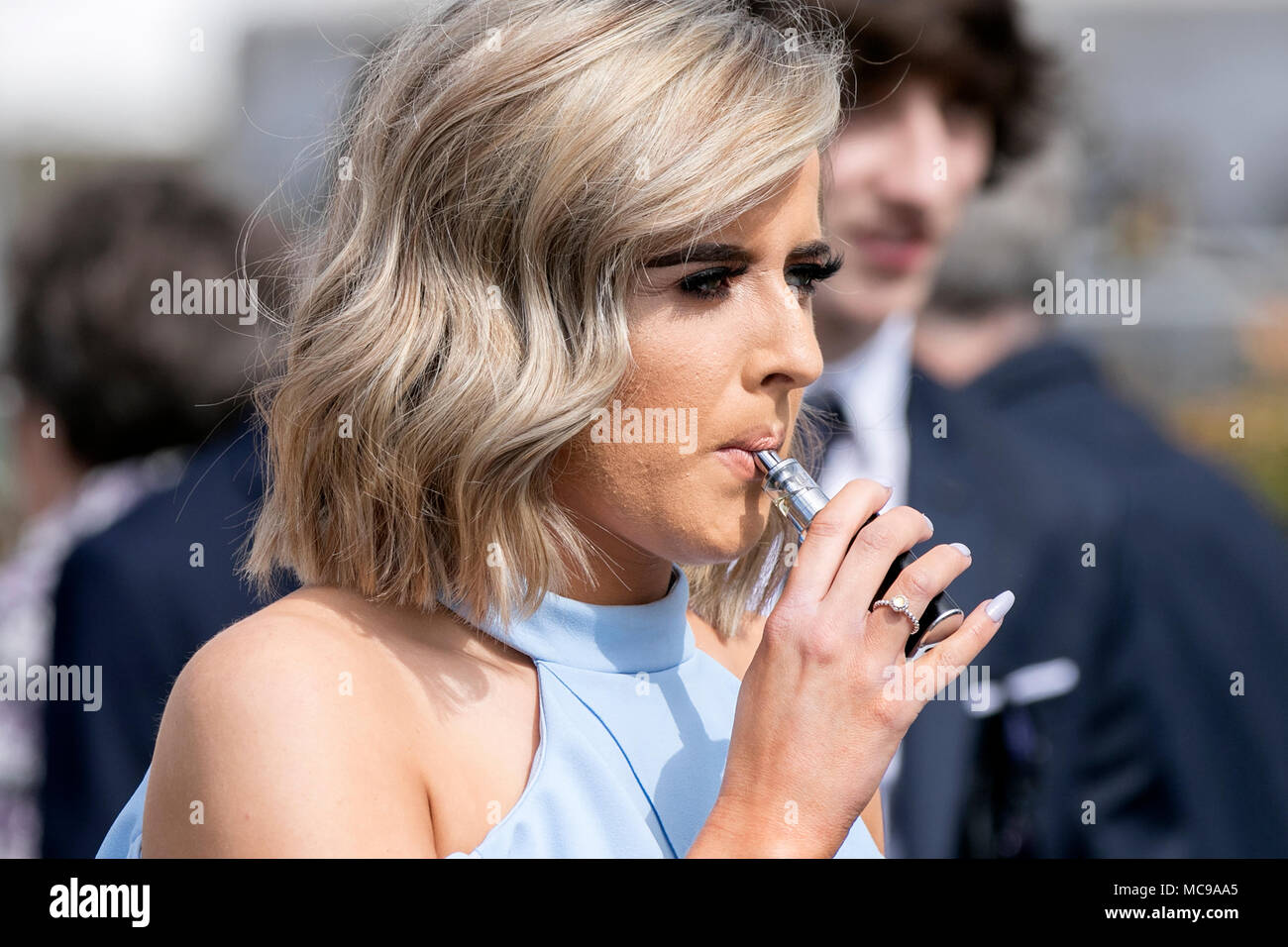 a young woman vaping on an e-cigarette vape device smoking substitute - Stock Image