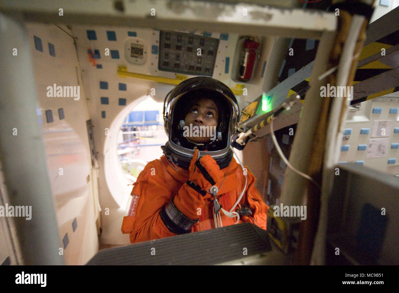 NASA astronaut Stephanie Wilson is attired in a training version of her shuttle launch and entry suit, as she participates in a training session in the Space Vehicle Mock-up Facility at the Johnson Space Center in preparation for the STS-131 mission. - Stock Image