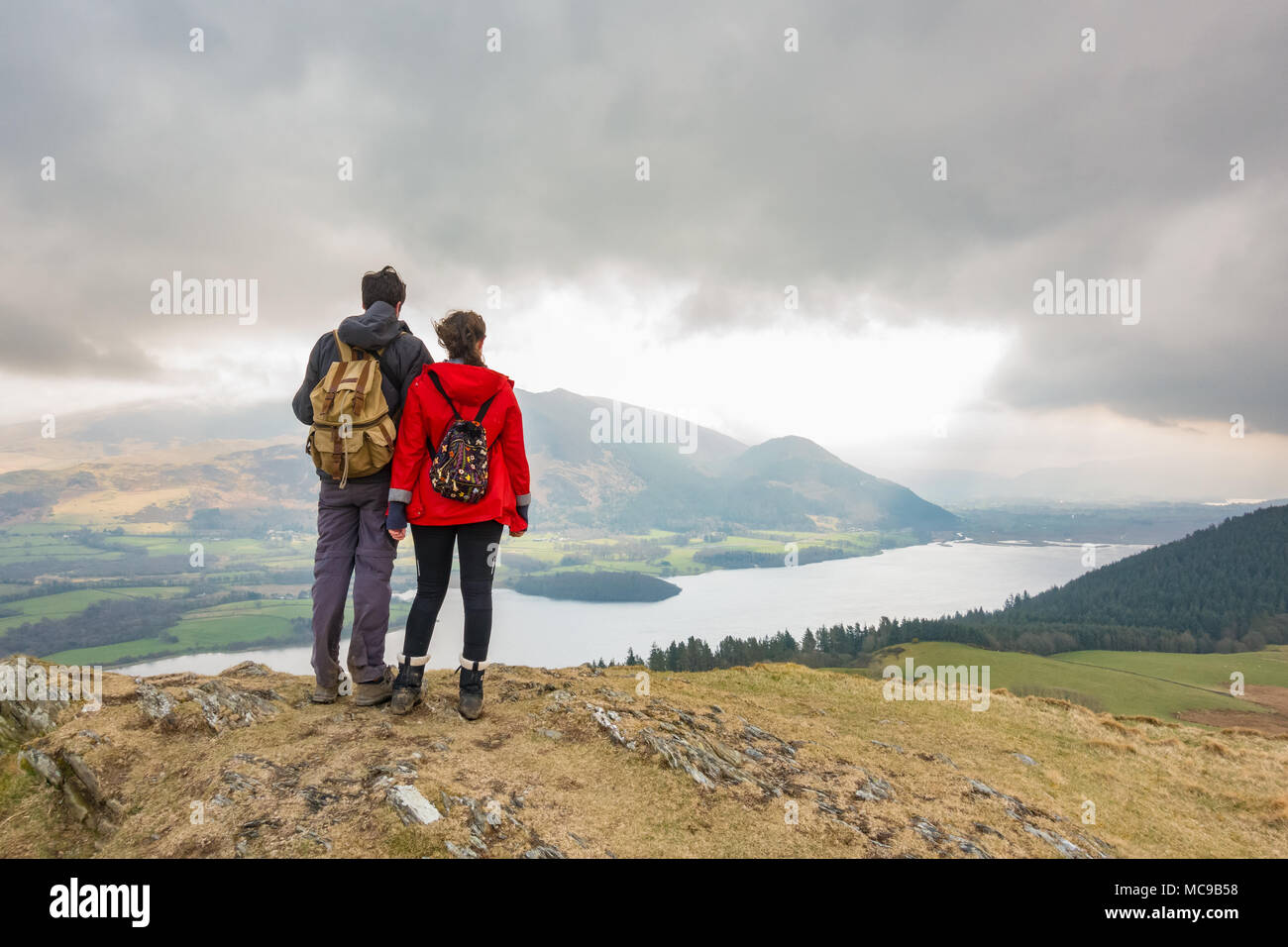 Lake district view - two walkers looking at the view of Bassenthwaite Lake and the Skiddaw range from Sale Fell, Lake District, Cumbria, England, UK - Stock Image