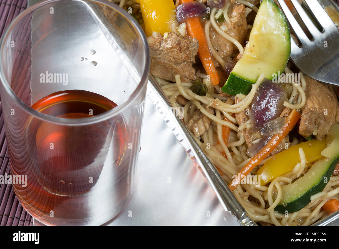 Chinese takeaway of Chicken noodle stir fry in a foil delivery dish with a glass of Saki - Stock Image