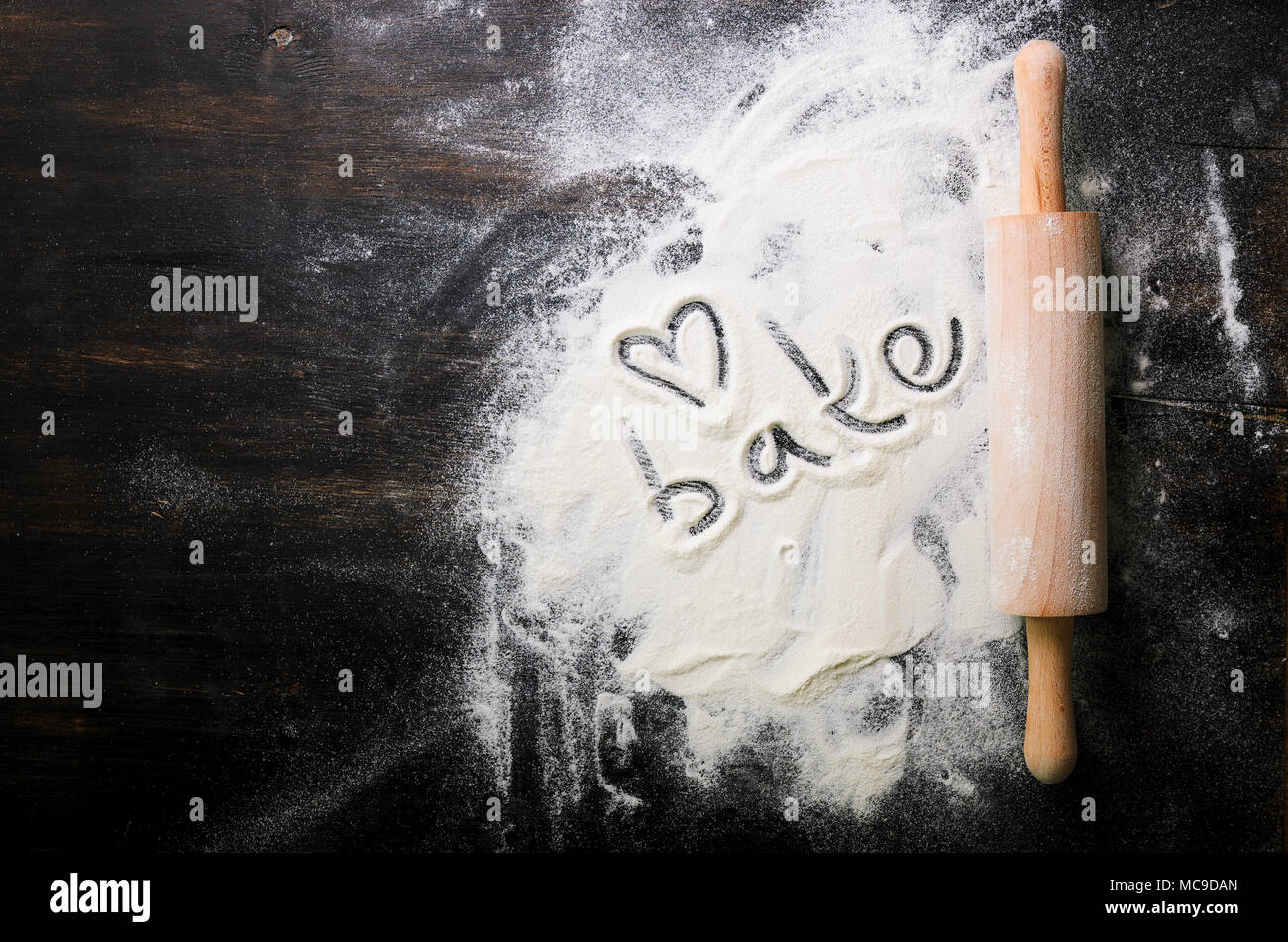 Baking background. Heart of flour, text Cook and rolling pin on dark table with copy space, top view Stock Photo