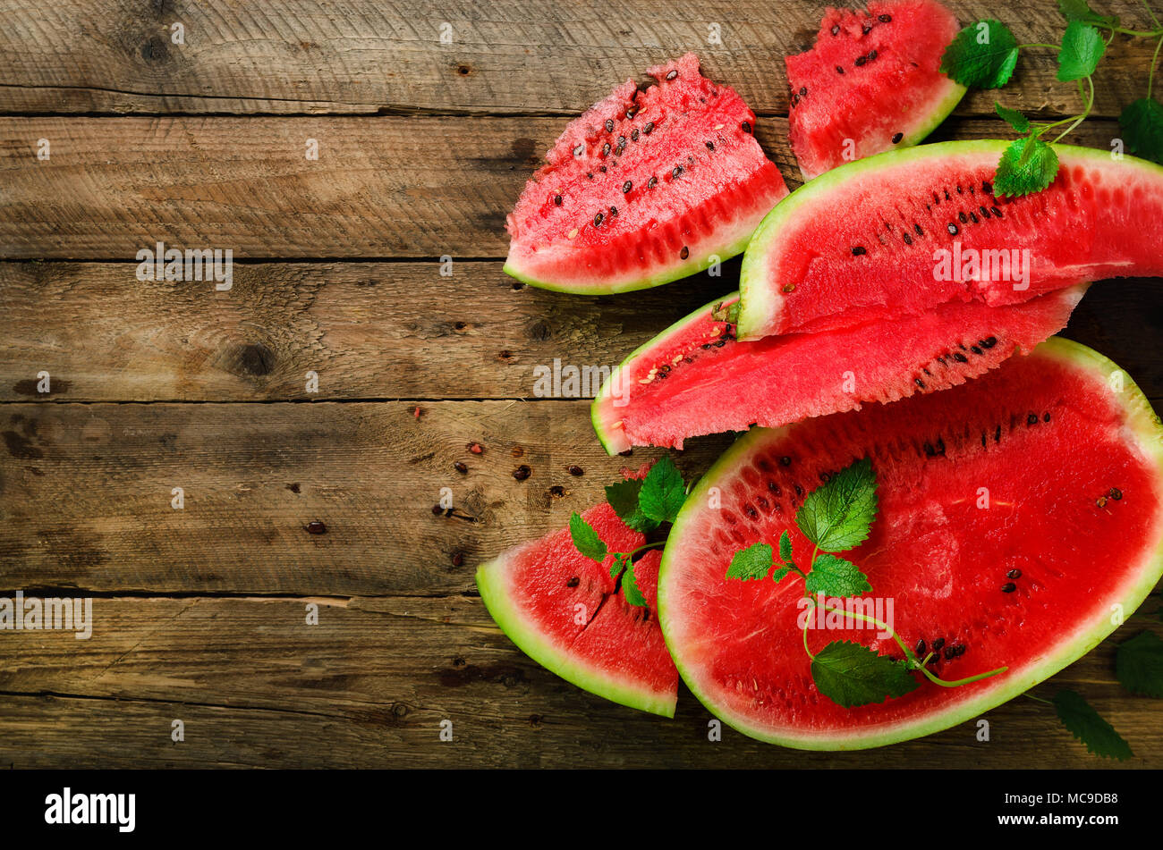 Slices of watermelon with mint leaves on wooden background. Detox and vegetarian concept. Top view, flat lay, copy space - Stock Image