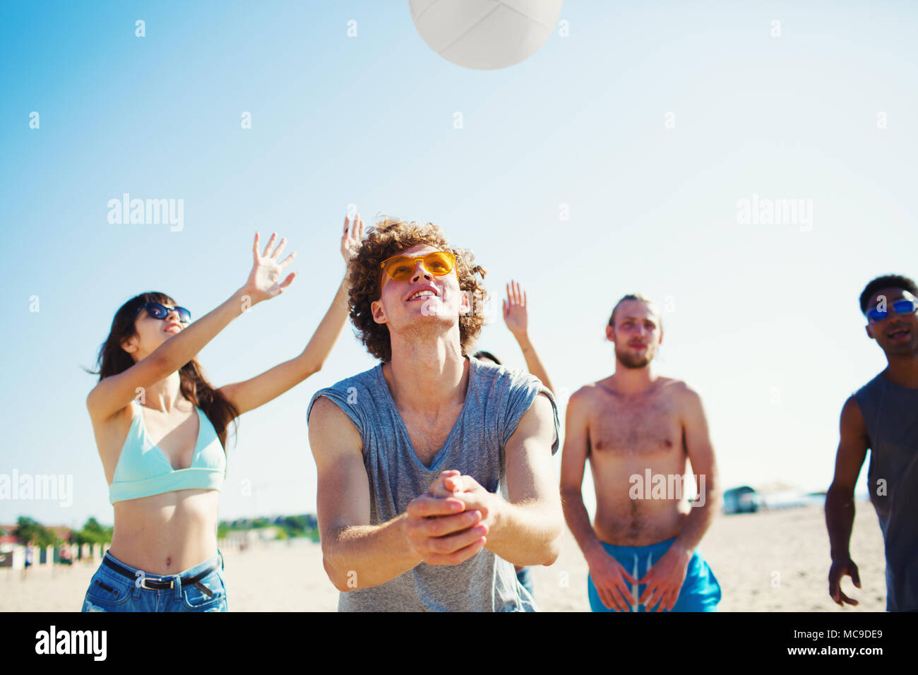 Group of friends playing at beach volley at the beach - Stock Image