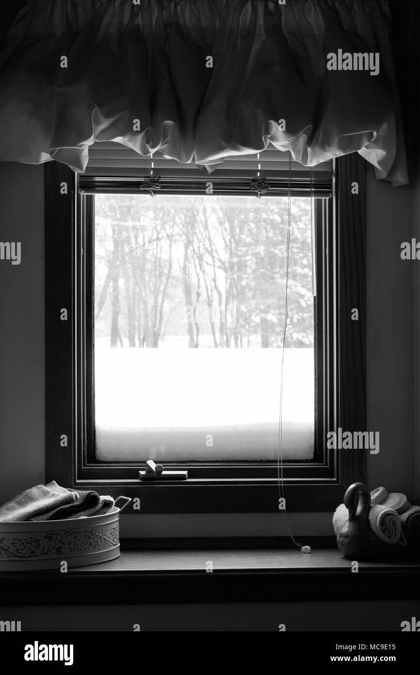 A window view of a winter blizzard from inside a cozy room - Stock Image