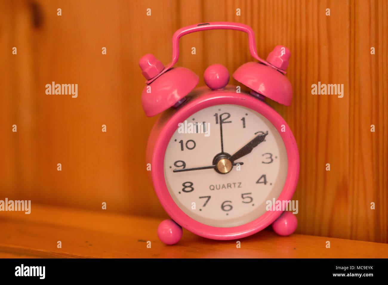 2566c4b7da3769 Pink Retro alarm clock on table