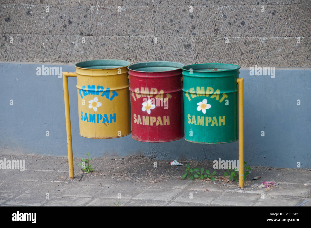Three recycle bins in Bali. The word Tempat Sampah means Trash Can. - Stock Image